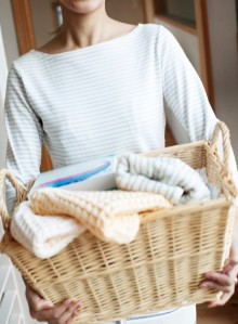 Woman Holding Laundry Basket Full of Towels